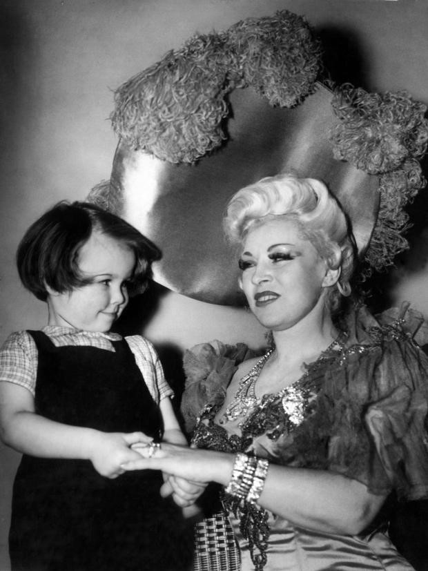 Mae West appears, with her platinum blonde hair and a large shiny hat, smiling at a young girl with a bob haircut and holding her hand.