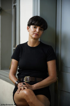 Ángeles, seated on a high stool in the center of the frame, is wearing a black shortsleeved shirt and dark jean shorts with a wide brown leather belt. She is wearing a leather bracelet and big rings, and her hands are clasped on her knee. Behind her is a white wall, a grey window frame, and a grey door.