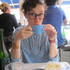 Katie, a curly-haired brunette White person with brown tortoiseshell glasses, a denim button-down and a double-strand necklace, is sipping tea with both hands and looking at the camera.